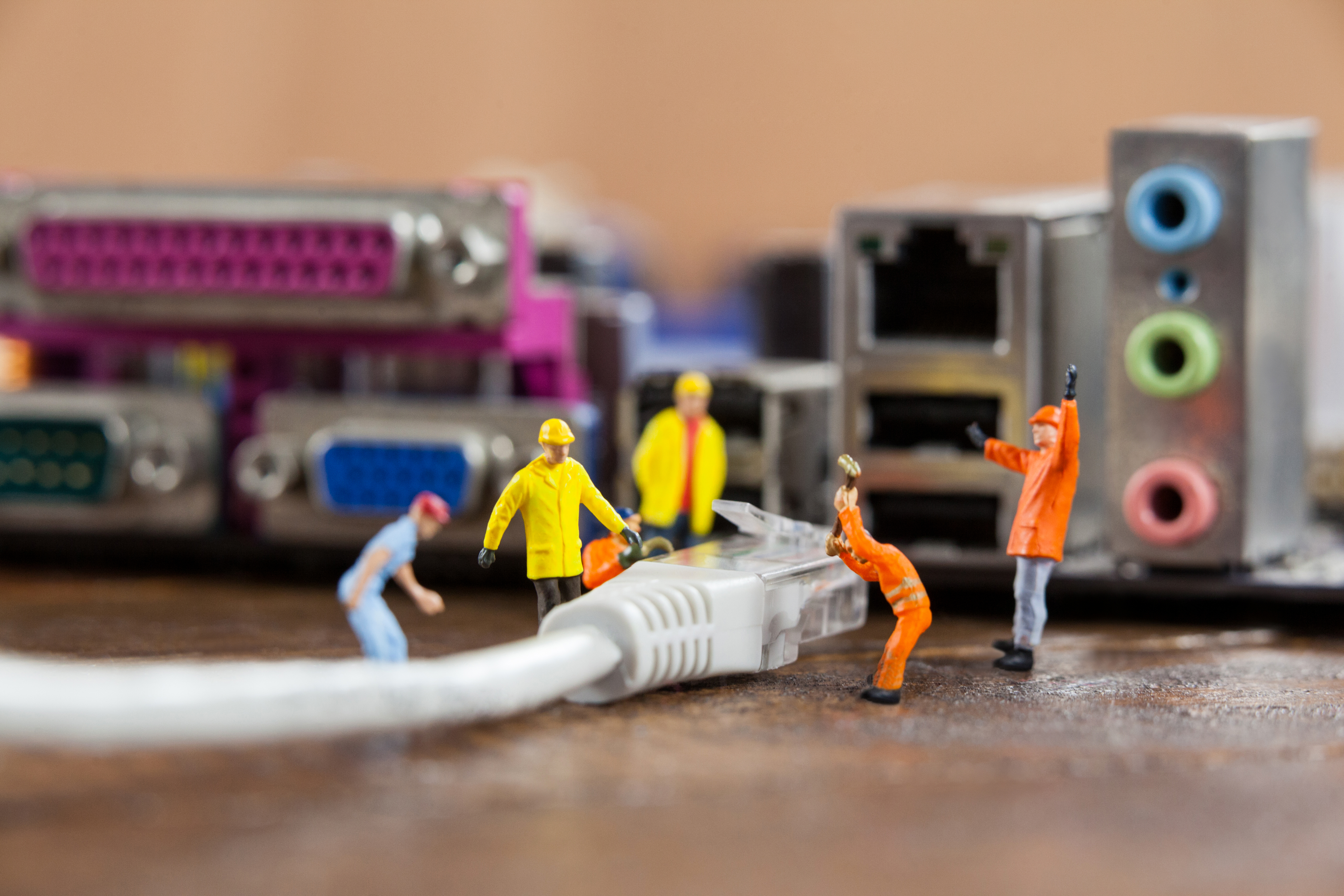 miniature-engineer-and-worker-plug-in-lan-cable-to-computer